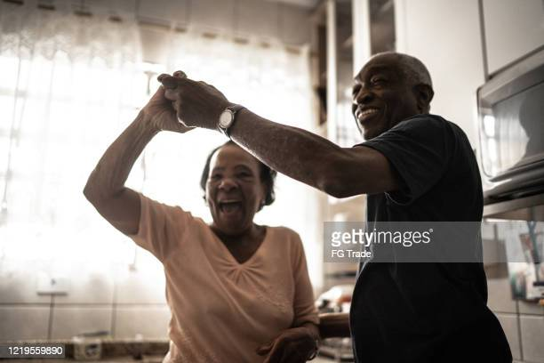 senior couple dancing at kitchen - life events stock pictures, royalty-free photos & images