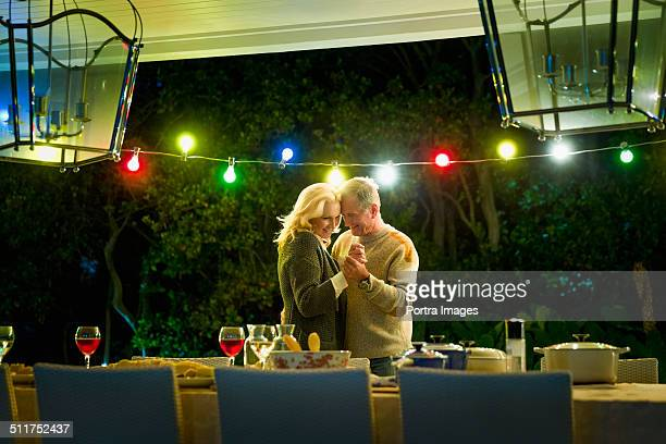 Senior couple dancing at table on porch