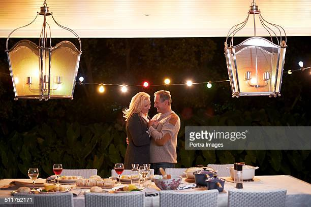 Senior couple dancing in front of dining table
