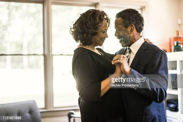 senior couple dancing in living room - young at heart woman fotografías e imágenes de stock