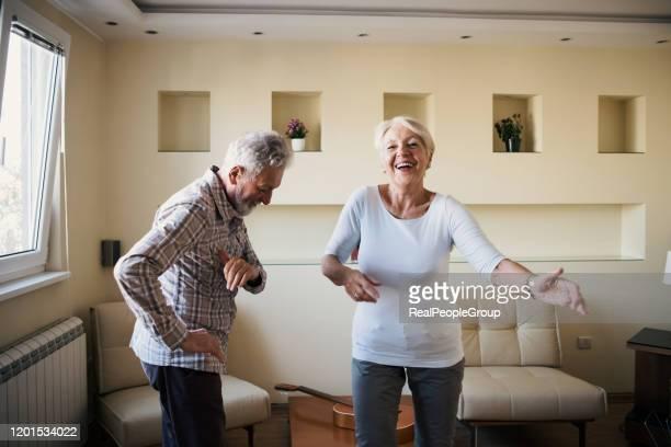 hoger paar dat in woonkamer danst - gewalt stockfoto's en -beelden