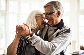 Senior couple dancing in living room