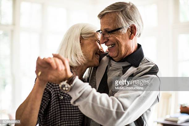 Senior couple dancing in living room