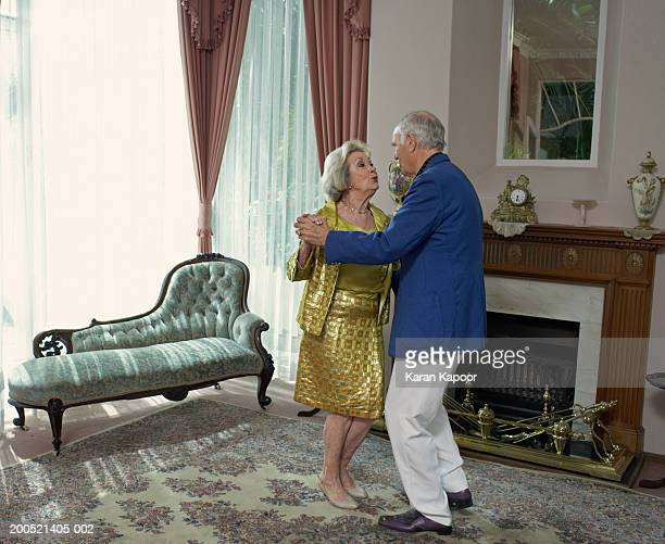 Senior couple dancing in living room, side view