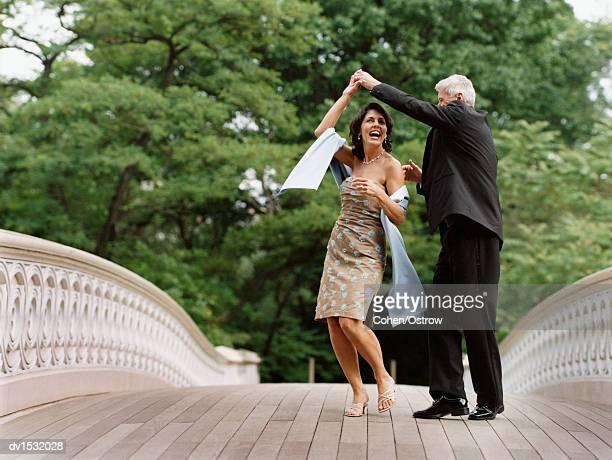 Senior Couple Dancing on Bow Bridge, Central Park, New York City, USA