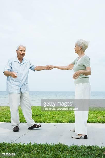 Senior couple dancing on sidewalk overlooking ocean, full length