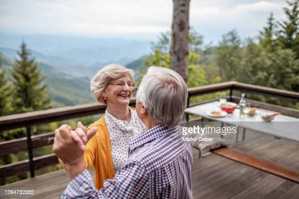 senior couple dancing on the patio - retirement stock pictures, royalty-free photos & images
