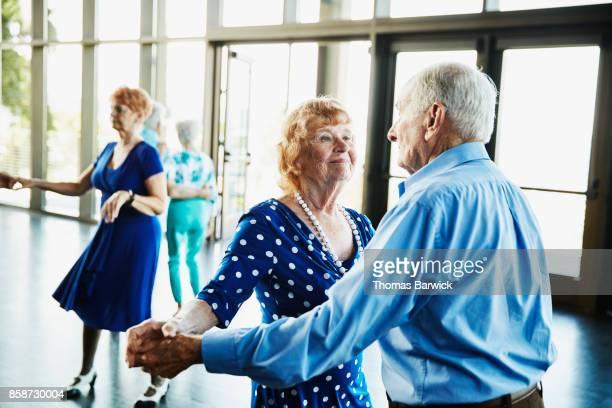 Senior couple dancing together during celebration in community center