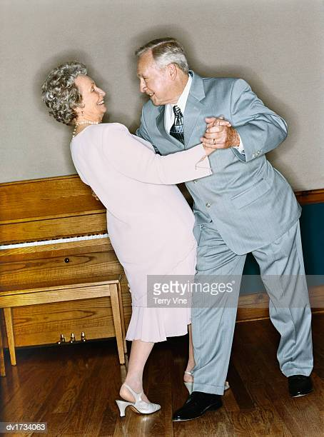 Senior Couple Dancing Together, with a Piano in the Background