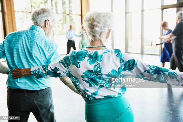 senior couple dancing with friends in community center - balzaal stockfoto's en -beelden