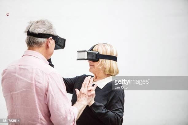 Senior couple dancing with virtual reality smartphone