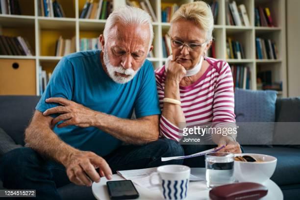 senior-paar beschäftigt sich mit hausfinanzen - geld und finanzen stock-fotos und bilder