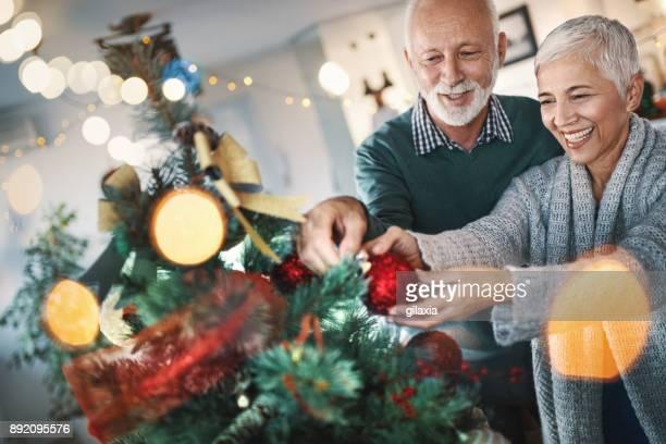 Senior paar versieren van een kerstboom.