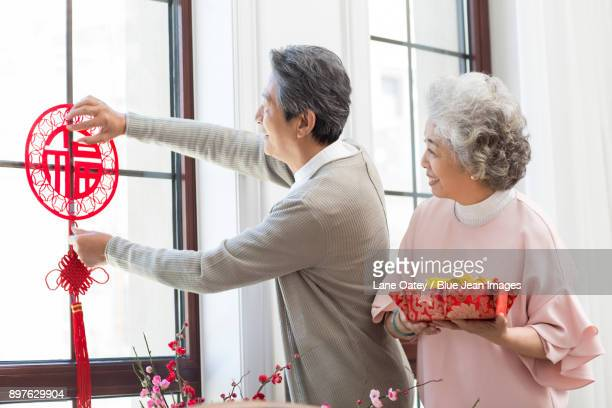senior couple decorating their house for chinese new year - chinese knotting stock pictures, royalty-free photos & images
