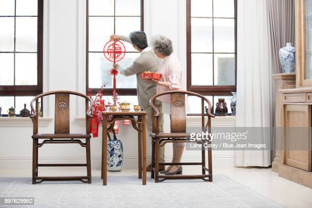 Senior couple decorating their house for Chinese New Year