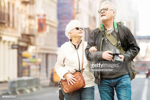 senior couple discovering broadway in new-york city in autumn - broadway manhattan stock pictures, royalty-free photos & images