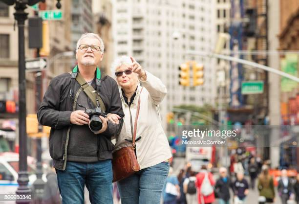 senior couple discovering new-york city in autumn - broadway manhattan stock photos and pictures