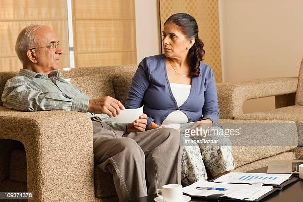 Altes Paar diskutieren Dokument im Wohnzimmer