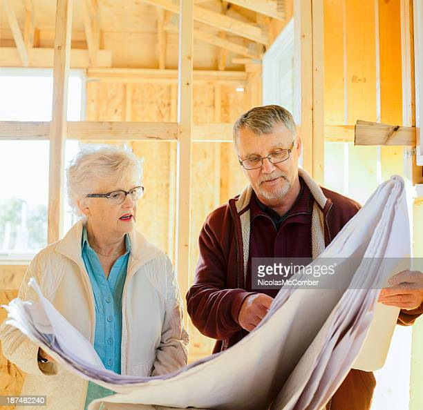 Senior couple discussing the plans of their new home