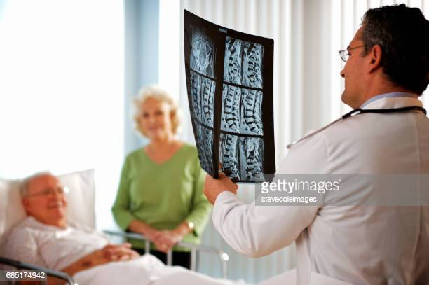 senior couple discussing x-ray with doctor. - spinal cord stock photos and pictures