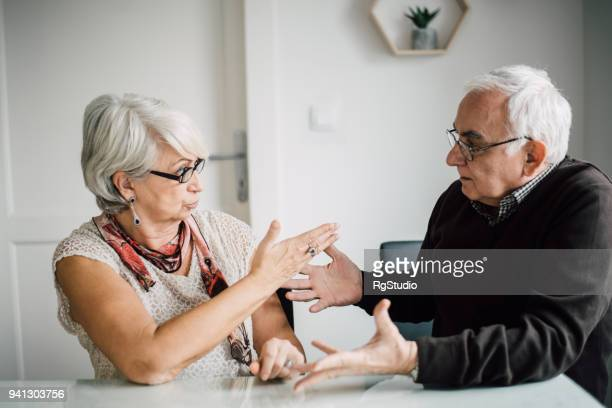 senior couple dispute - couple arguing stock photos and pictures