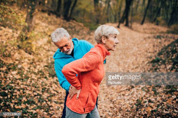 senior couple doing back exercises - back pain stock pictures, royalty-free photos & images