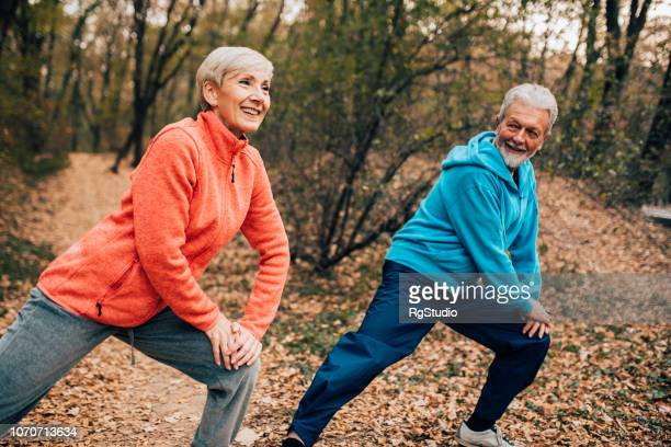Senior couple doing calf stretches in a park