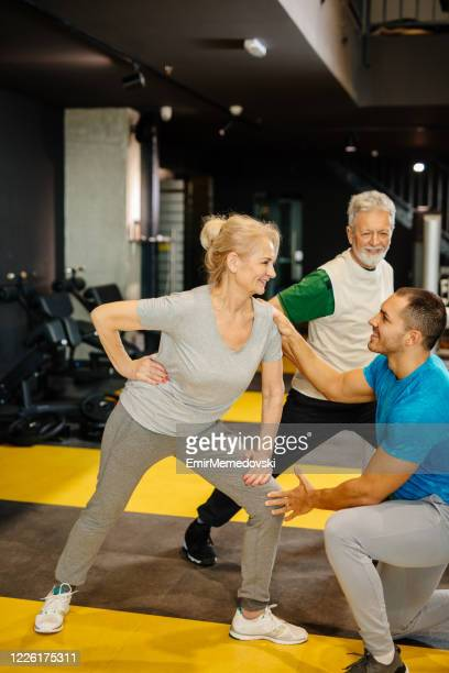 senior couple doing exercises with personal trainer at the gym - doing a favor stock pictures, royalty-free photos & images
