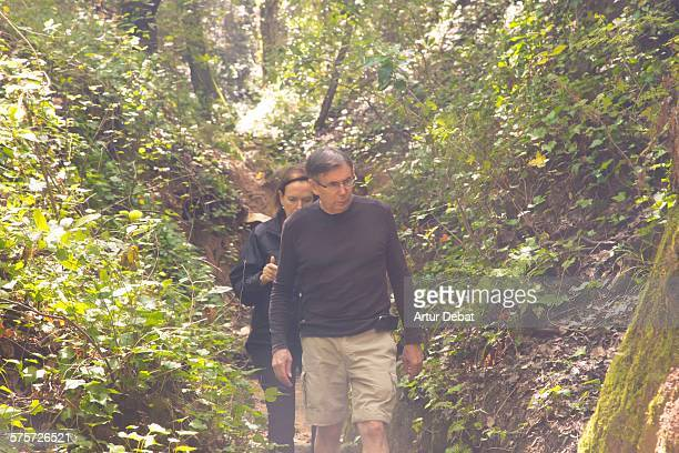 senior couple doing hiking between the nature. - between stock pictures, royalty-free photos & images