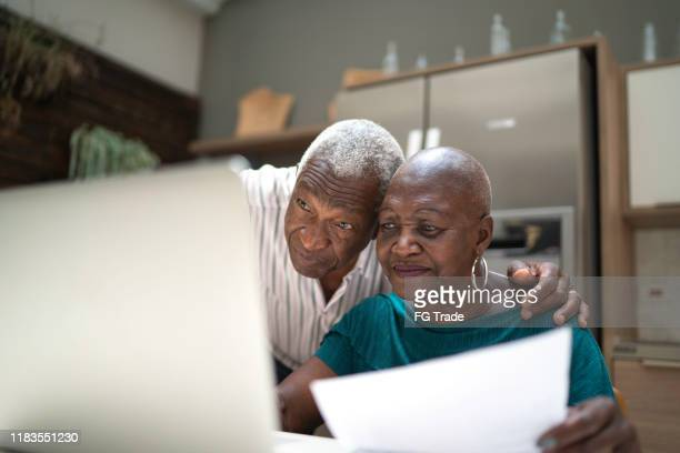 senior couple doing home finances - bank account stock pictures, royalty-free photos & images