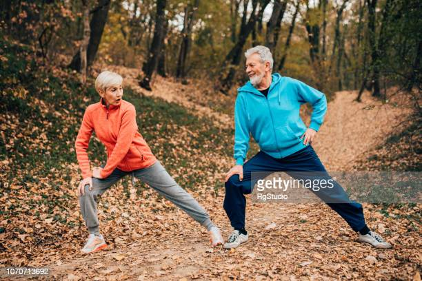Senior couple doing leg stretches in a park