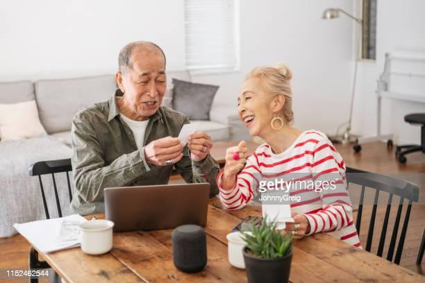 自宅で、笑顔でオンラインバンキングを行うシニアカップル - cheerful ストックフォトと画像