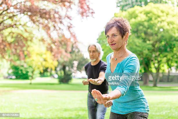 Senior couple doing tai chi in park, Tübingen, Germany