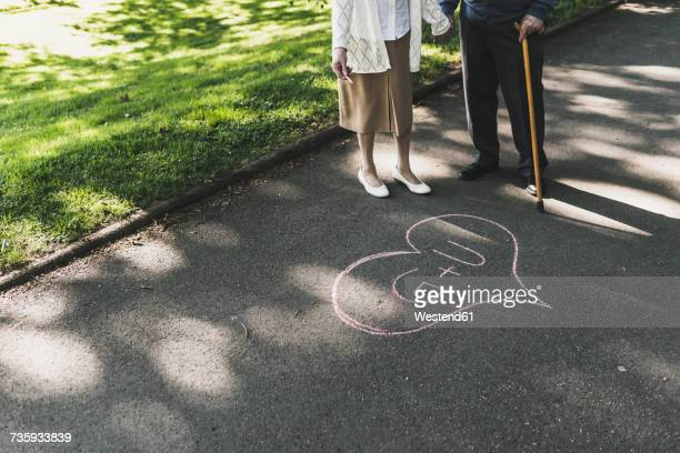 Senior couple drawed love heart with initials on tarmac