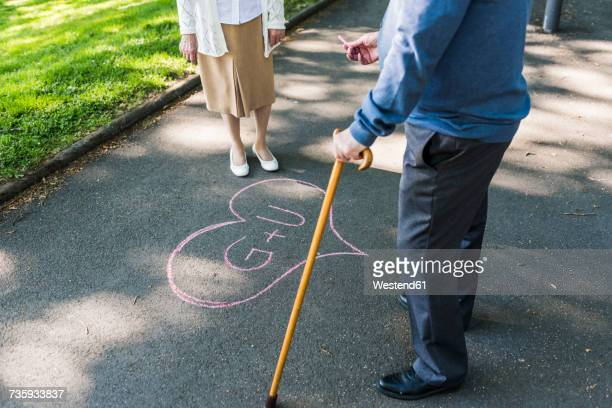 Senior couple drawing love heart with initials on tarmac