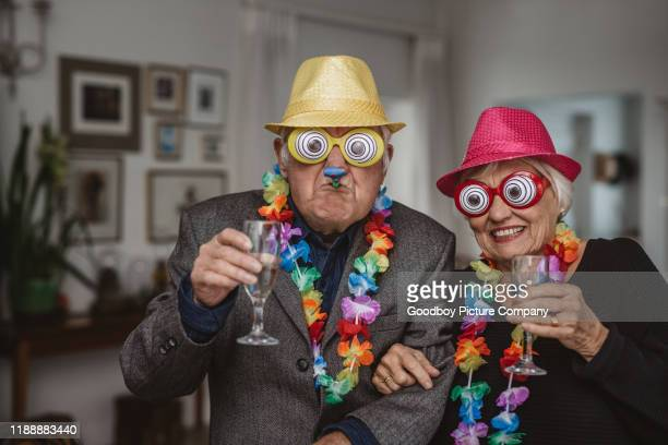 senior couple drinking and wearing novelty glasses at a party - funny stock pictures, royalty-free photos & images