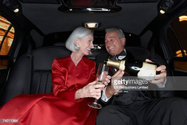 senior couple drinking champagne in limousine - millionnaire stock pictures, royalty-free photos & images