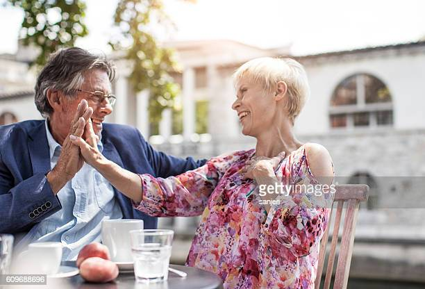 Senior Couple Drinking Coffe and Chatting at a Sidewalk Cafe