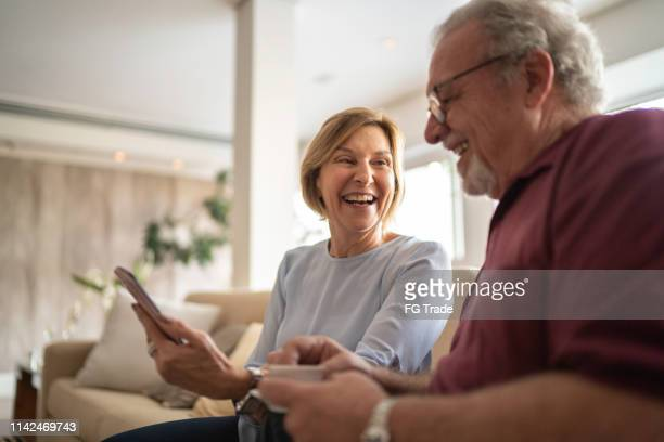 senior couple drinking coffee and using cellphone - part of a series stock pictures, royalty-free photos & images
