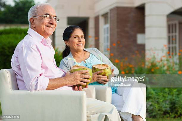 Senior couple drinking from coconuts in garden