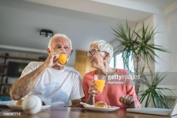 senior couple drinking orange juice during breakfast - orange juice stock pictures, royalty-free photos & images