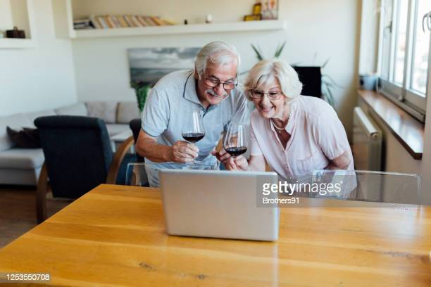 senior couple drinking wine and chatting with friends and family online - wine tasting stock pictures, royalty-free photos & images