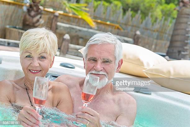 年配のカップルがかたまってワインを飲んで、ジェットバス