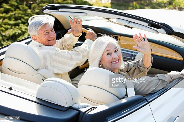 Senior couple driving away in convertible