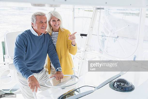 Senior couple driving boat, looking ahead, pointing