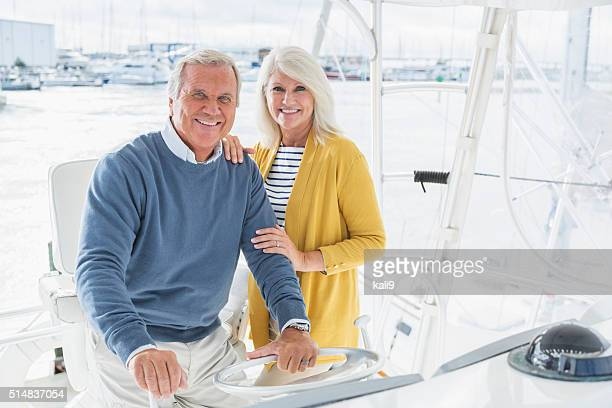 Senior couple driving boat out of marina