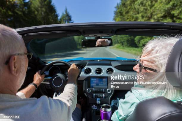 Senior couple driving in convertible