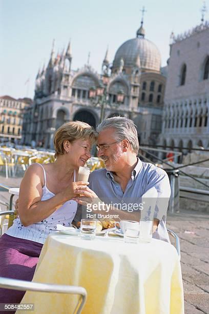 Senior couple eating at sidewalk cafe, St. Mark's Square, Venice, Veneto, Italy