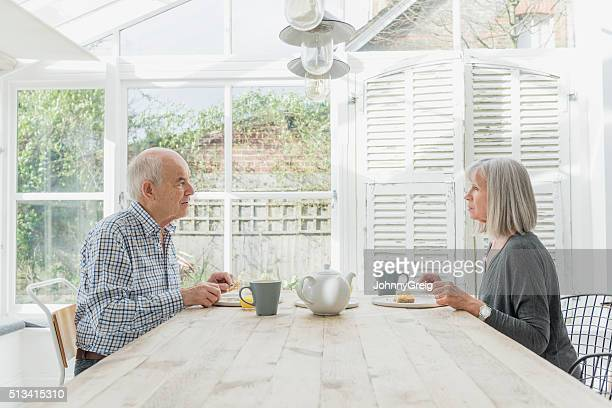 Senior couple eating breakfast in a conservatory