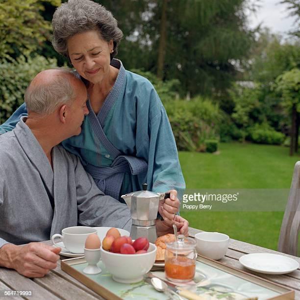 Senior Couple Eating Breakfast in Garden